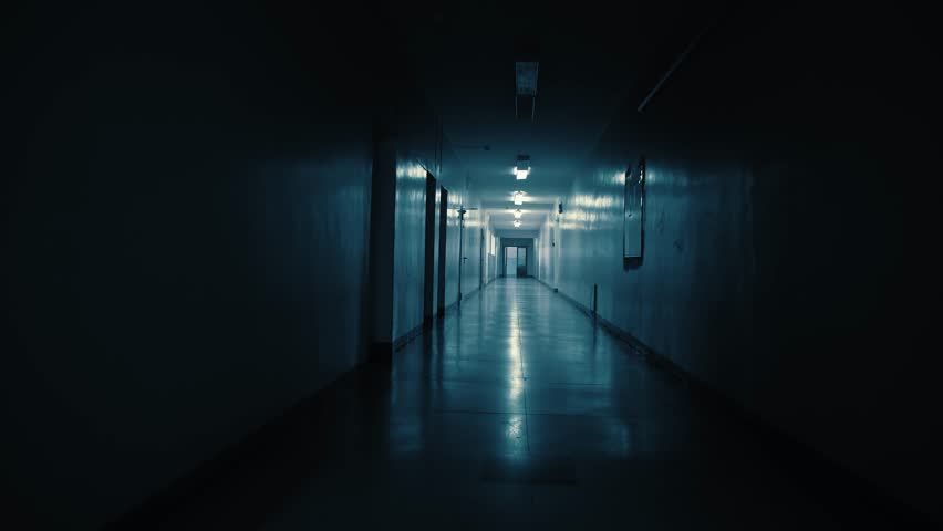Tracking inside a long dark gloomy corridor, tunnel past the small windows to the old ajar doors with glass inserts. Concept of horror.