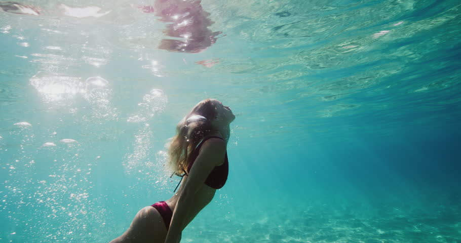 Beautiful woman swimming under the ocean's surface with sandy ocean floor and sunlight, active healthy fitness lifestyle