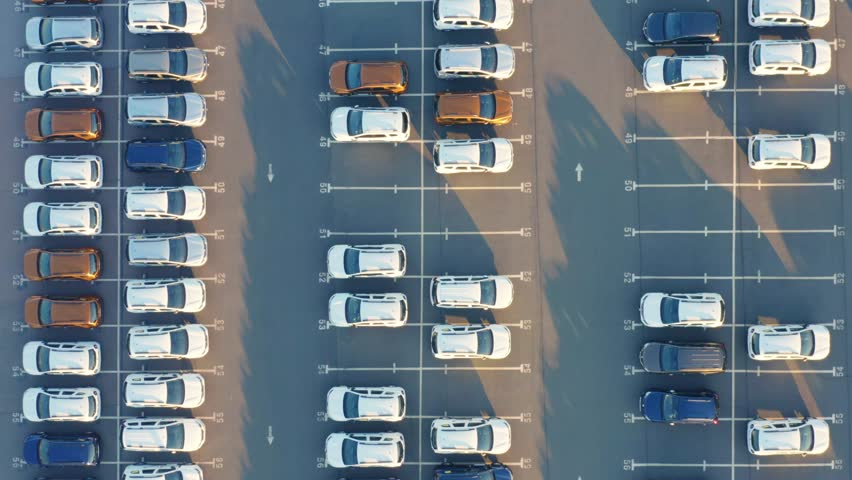 Aerial top view of the dealership terminal parking lot with a rows of new cars on a sunny day