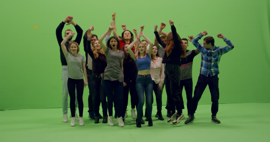 GREEN SCREEN CHROMA KEY Front view group of young people dancing and jumping with hands in the air. 4K UHD ProRes 4444