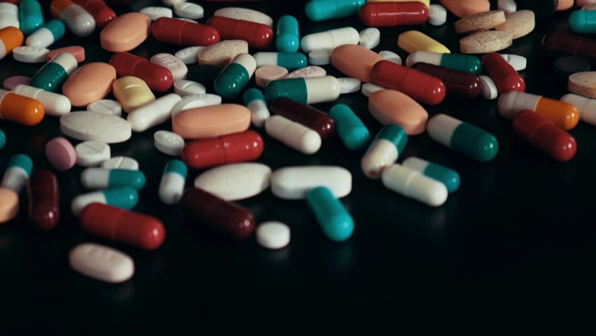 Multicolor pills and capsules on a black table   Shutterstock HD Video #1027038956