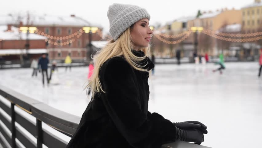 Portrait of young woman looking at camera and smiling. Ice rink on background #1027039511