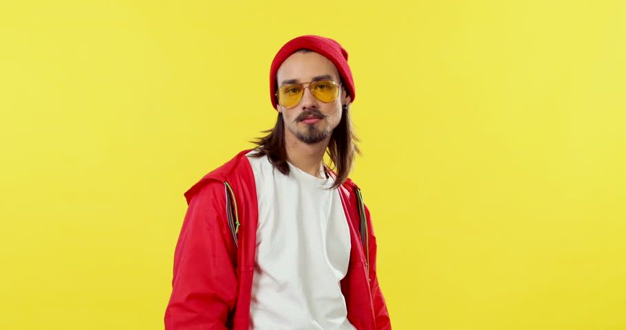 Caucasian young handsome hipster man in the red hoodie, hat and sunglasses having fun and showing off in front of the camera on the yellow back wall. Portrait shot. | Shutterstock HD Video #1027041425
