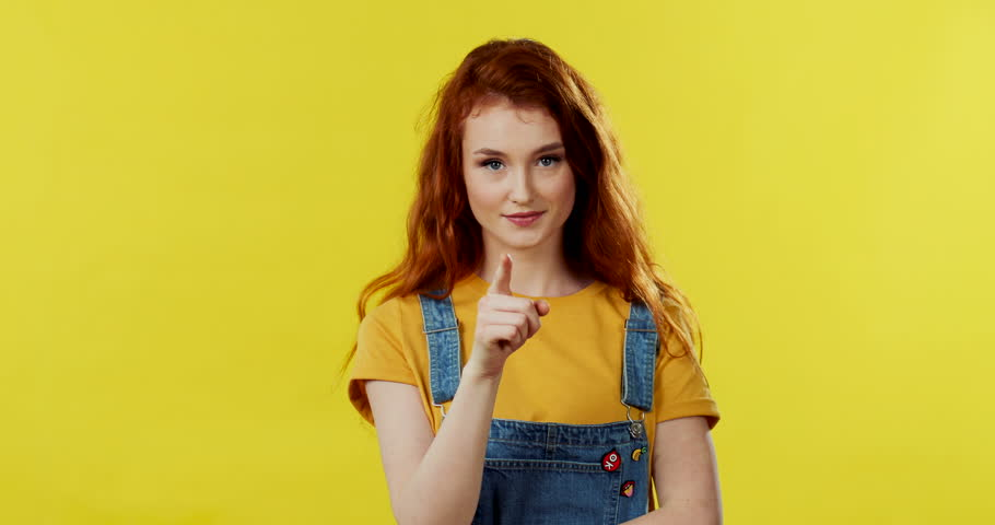 Portrait shot of the charming Caucasian young red haired woman standing in front of the camera and doing a gesture with her finger to mouth like be silent, hush, then smiling cheerfully on the yellow | Shutterstock HD Video #1027042070