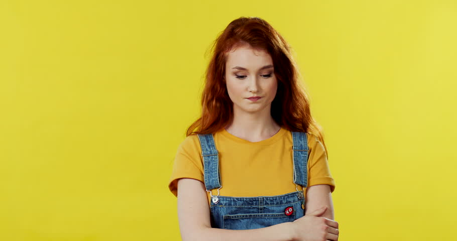 Young Caucasian attractive girl with red hair standing on the yellow wall background and worrying a lot about something. | Shutterstock HD Video #1027042082