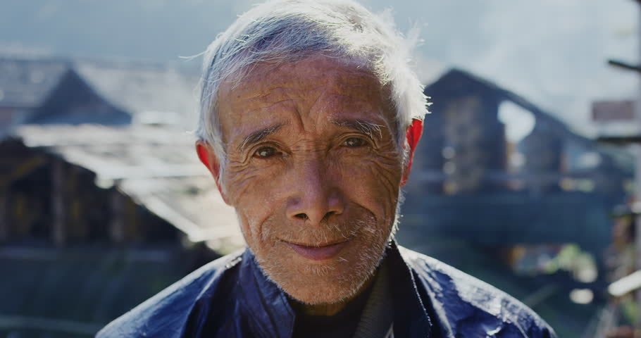 Timeless portrait of a real unique authentic Asian Chinese village man, rice farmer, background is Huanggang mountain village China. Hand held, Red cinema camera, slow motion.