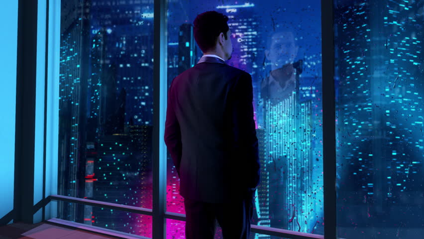 In the near future, thoughtful Businessman wearing a suit standing in his office, looking out of the window and staring at a futuristic city with skyscrapers and colorful lights. | Shutterstock HD Video #1027051820