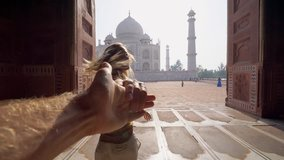 Follow me to the Taj Mahal, India. Female tourist leading boyfriend to there magnificent famous Mausoleum in Agra. People travel concept .leading the way