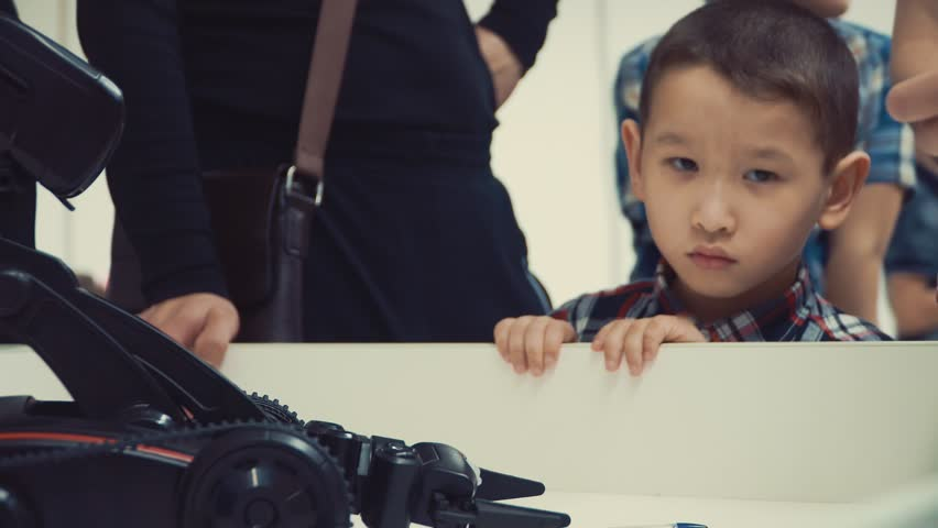 Asian boy watching the robot on the table at the exhibition. | Shutterstock HD Video #1027058582