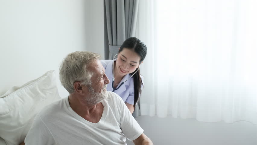 Grandfather or senior man on bed and nurse coming to senior man and do health check and discussion with smiling together in white room and grey curtain background | Shutterstock HD Video #1027067021