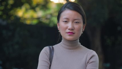 front view of one young asian woman looking at camera smile in the afternoon sunlight. young joyful Chinese businesswoman smile at camera in the Chengdu city street, real people portrait 4k clips
