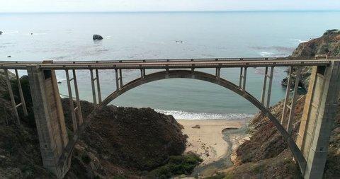 Aerial Drone Stock Video of Bixby Bridge Highway with water and shore below in Big Sur Monterrey California