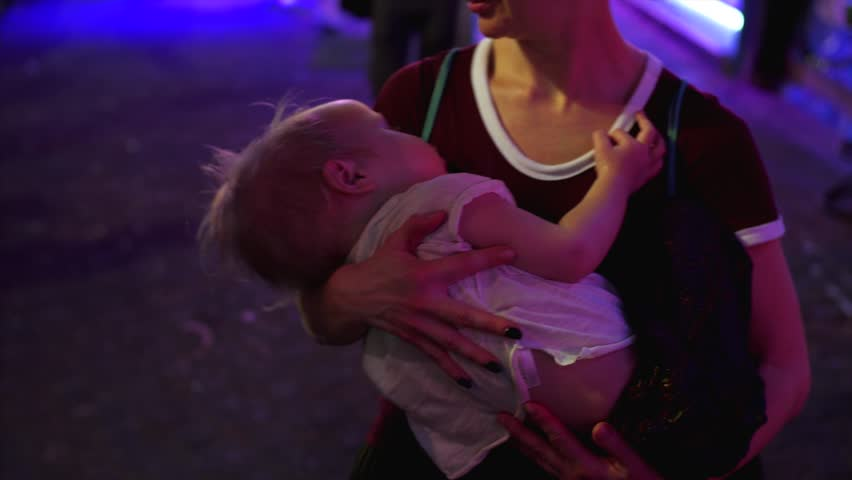 Mother is lulling her little child holding him in arms in the evening street of Pattaya, Thailand.