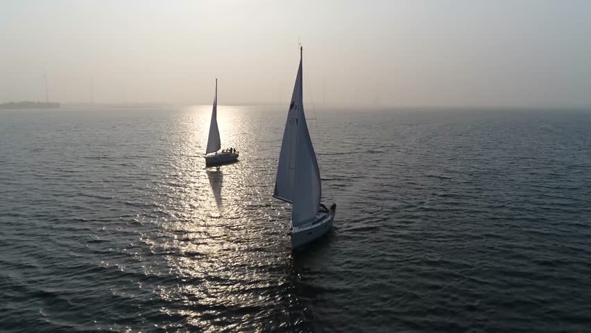 Aerial view of two sloops at sundown are sailing boats with single mast and fore-and-aft rig plus one head-sail the most common setup of modern sailboats is the Bermuda-rigged configuration 4k quality #1027128272