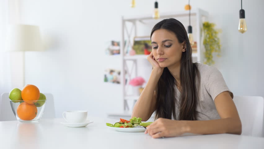 Dissatisfied woman looking on salad, healthy low-calorie diet for weight loss