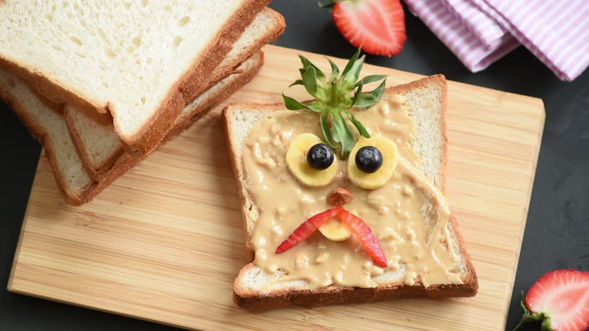 Stop motion animation of making peanut butter toast with funny angry bird face for kids school lunch. Back to school lunch idea