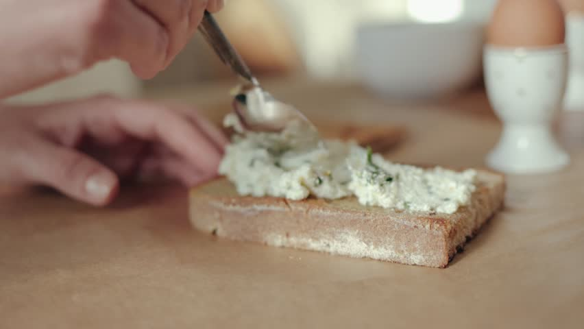 Female chef putting cheese spread on a toasted whole wheat bread 4k   Shutterstock HD Video #1027142474