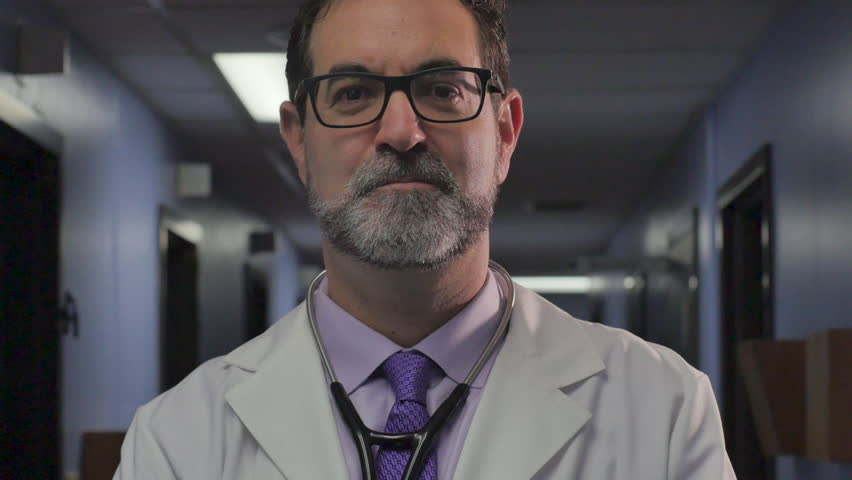 Portrait of a handsome, sophisticated, male doctor with a stethoscope around his neck smiling, nodding his head yes, and looking at the camera in a clinic or hospital in slow motion