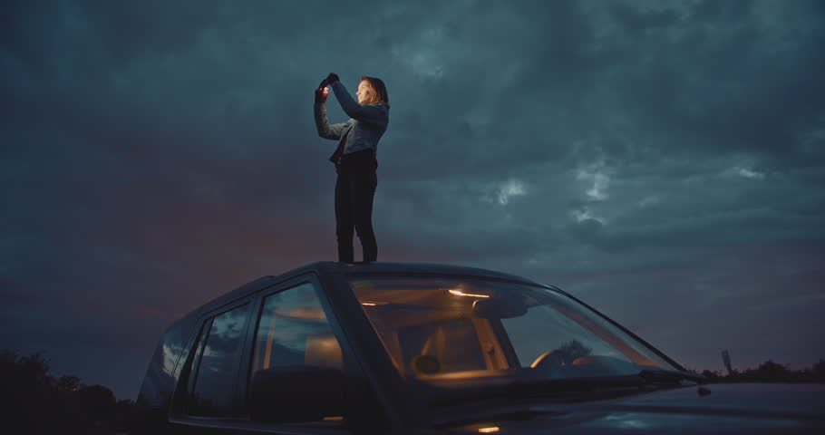 Young woman taking panoramic photo on smartphone device or catches signal on her mobile phone searching interesting places in mountains, slow motion, shot on cine camera 4K | Shutterstock HD Video #1027149917