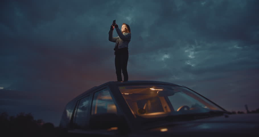 Slow Down To Enjoy Your Trip, Traveler woman takes pictures at night on smartphone device while standing on the roof of the car, Connection in Mountains, Cinematic Shot #1027149923