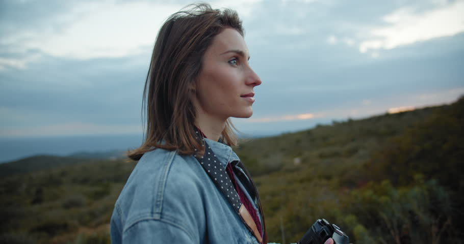Outdoor spring smiling lifestyle shot of pretty young woman taking photos of sunset in the mountains in Europe, travel photographer making pictures at evening, slow motion, cine camera 4K   Shutterstock HD Video #1027149926