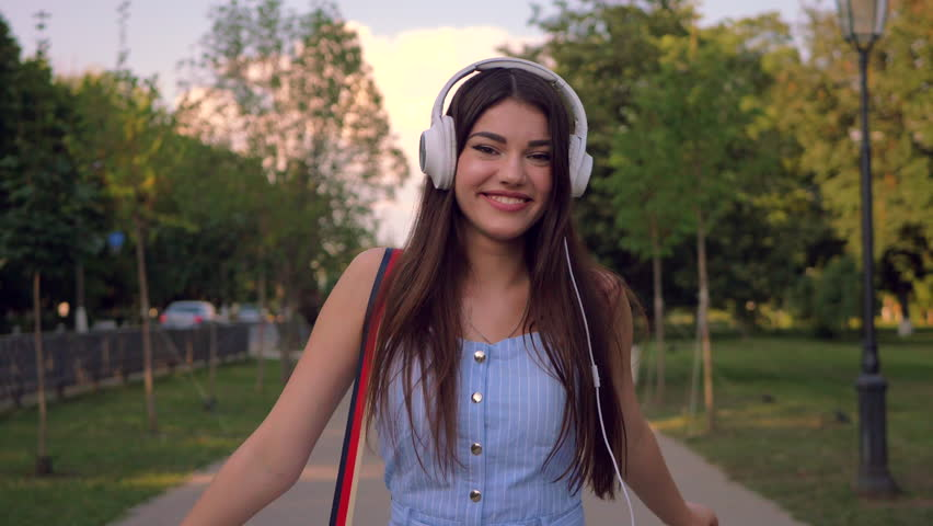 Enchanting lady is walking outdoors in park in summertime, listening to music in her headphones. Stylish woman is wearing blue romper suite.    Shutterstock HD Video #1027157513