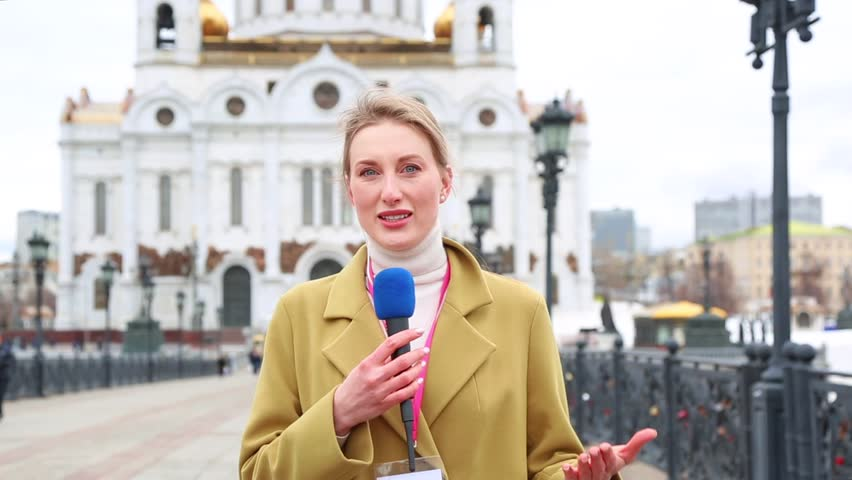 Caucasian female news reporter with microphone reporting news story on street
