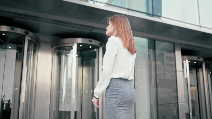 Anonymous Slender Caucasian Business Woman Manager in White Shirt is Entering into Office Building via Glass Revolving Door. Back View Low Angle 4K Slow Motion Corporate Shot   Shutterstock HD Video #1027184987