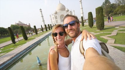 Young couple taking selfie portrait at the Taj Mahal international landmark in India- Man and woman takes selfie while traveling  having fun discovering and sightseeing