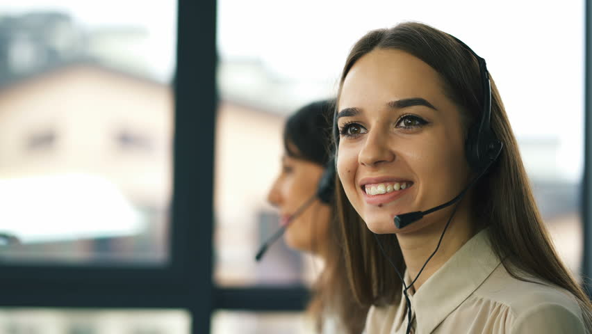 4K. Two young smiling women operators answer client. Office call center work process.