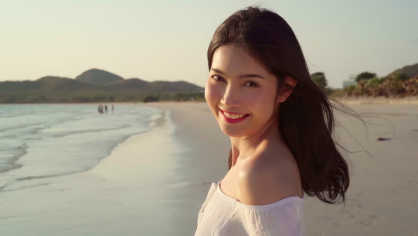 Slow motion - Young Asian woman walking on beach. Beautiful female happy relax walking on beach near sea when sunset in evening. Lifestyle women travel on beach concept.
