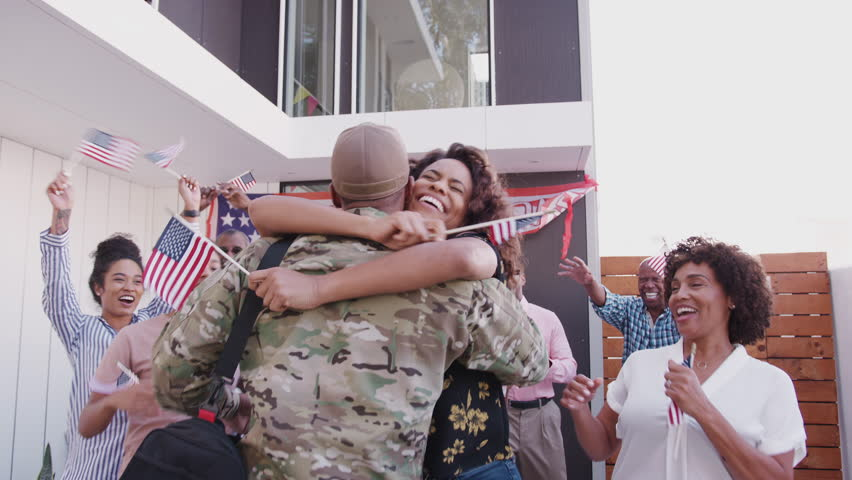 Black family running out of their house to greet a soldier returning home