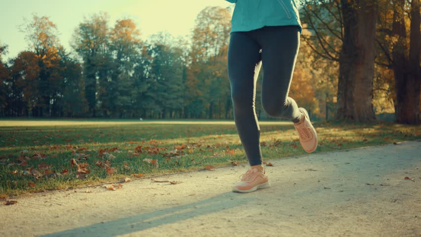 Running, close-up legs sport shoes, Woman runner walking in the autumn park on sunny day,  | Shutterstock HD Video #1027220927