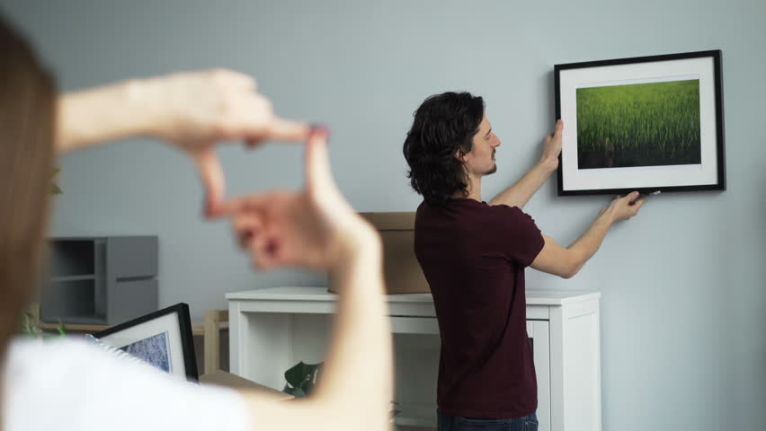 Handsome guy is picking place on wall to hang modern picture while his girlfriend is making frame with her fingers and gesturing approving his decision. #1027227122