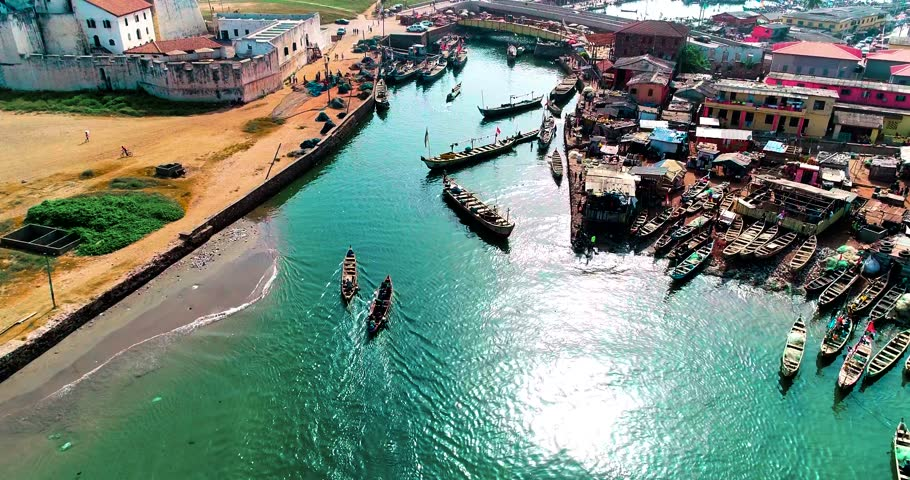 Local docks at Elmina, Ghana. Fishermen from sea entering local port, passing under bridge.