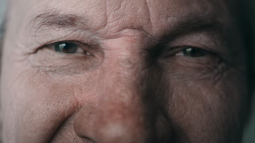 Close-up portrait of an old man. Eyes of an elderly man close-up. A grown man looks at the camera, blinks, smiles. Cool color, slow motion. 4K