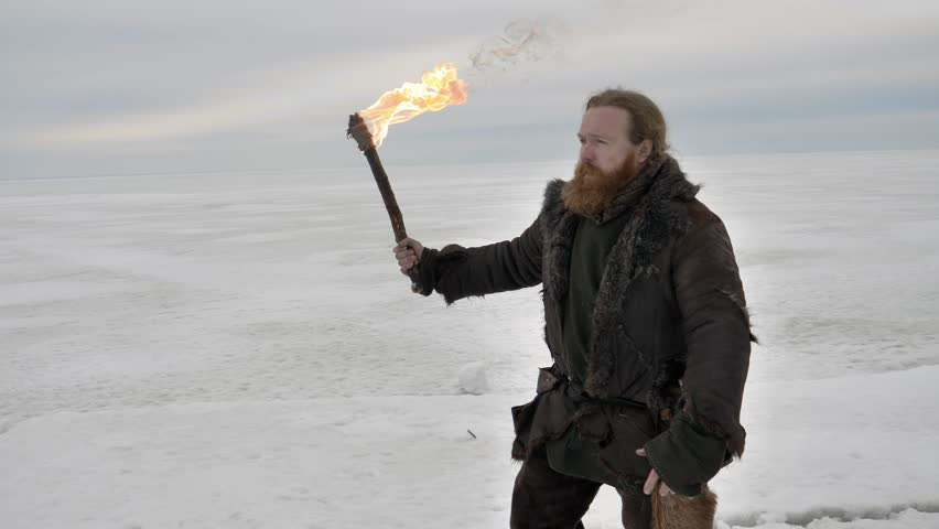 Fantasy winter episode. Medieval viking holding torch and walking over frozen ice.