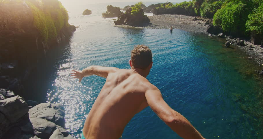 POV shot of young adventurous man cliff jumping into sunny blue pool in the jungle, POV adventure lifestyle