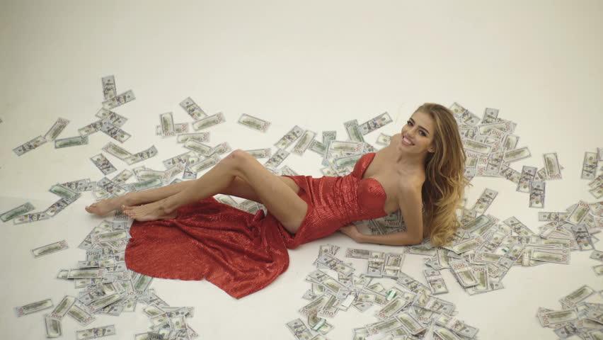 Currency, women, winning. Sexy woman lying in dollar bills. Girl in elegant red dress lying in banknotes. Rich woman lies on money. People, dollar, money, wealth and rich | Shutterstock HD Video #1027264265