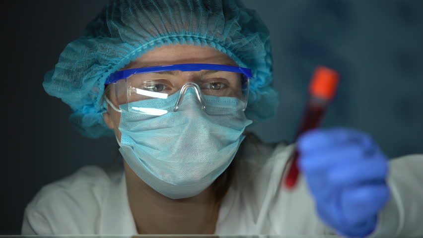 Medical lab worker analyzing blood serum, conducting paternity blood test, DNA
