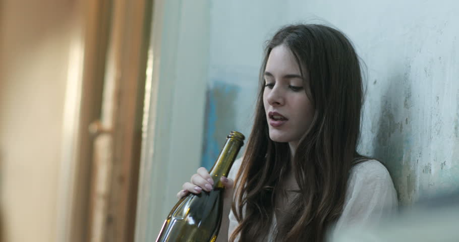 Woman in depression. Young brunette woman sits on the floor and drinks wine from a bottle crying. 4k | Shutterstock HD Video #1027292945