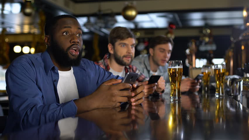 Men in bar celebrating successful bet on sports, using online bookmaker on phone Royalty-Free Stock Footage #1027297190
