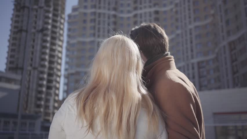 Beautiful young couple in love talking standing against the backdrop of a large modern residential building. | Shutterstock HD Video #1027299185