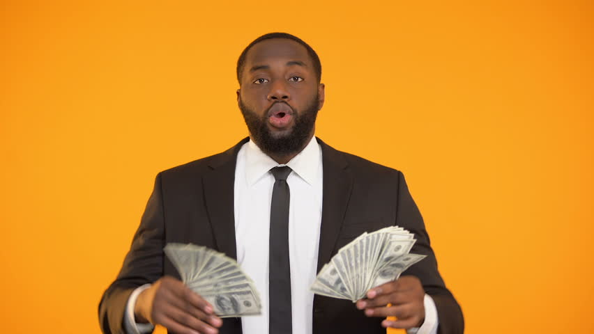 Afro-american male in formal suit making dancing movements with dollar cash