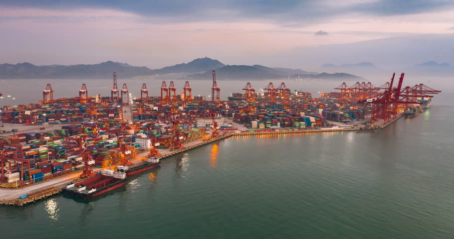 Time lapse aerial view of cargo terminal in Shenzhen,China. containers and cranes in the dock.The freight terminal is colorful in twilight.