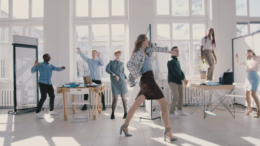 Young happy Caucasian female boss dancing in modern office celebrating together with multiethnic colleagues slow motion.
