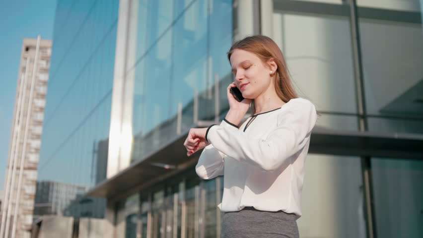 Adult Caucasian Confident Young Business Woman in White Shirt is Talking on Phone Outside near Modern Office Building. Medium Long Low Angle 4K Slow Motion Corporate Shot with Moving Around 360 Camera | Shutterstock HD Video #1027338185