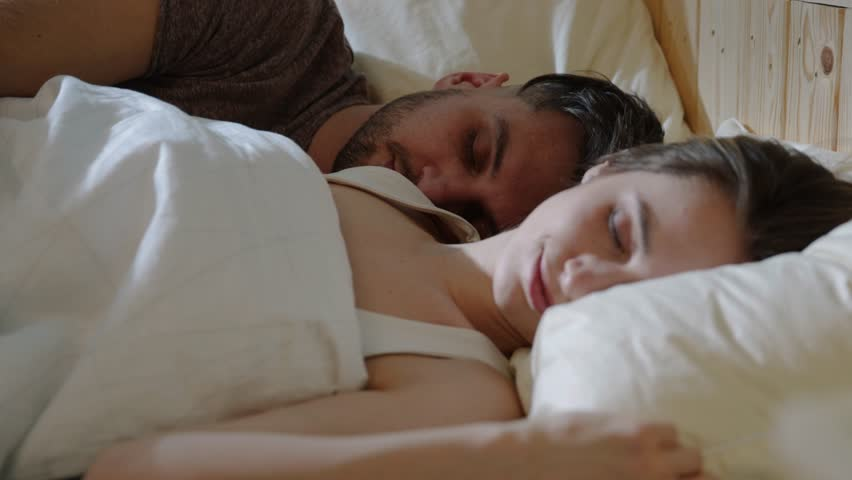 Close up view of sensual young couple sleeping in bed together, man wakes up first and kisses his beloved woman. Morning sunshine, couple goals, love, caring. Romantic atmosphere, happy atmosphere | Shutterstock HD Video #1027343297