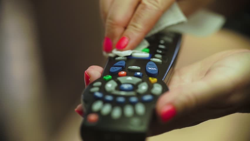 A female hand enters frame and wipes a television remote contnrol with a paper towel in sunlight. | Shutterstock HD Video #1027344560