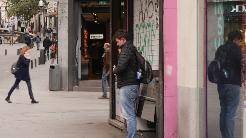 MADRID, SPAIN - APR 01, 2019: People on a street use mobile phone and eat snack food during walking | Shutterstock HD Video #1027361132